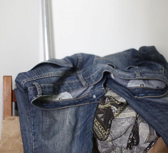 Ambiente interno, ao fundo parede de cor branca, caniço de metal recostado sobre a parede. Em frente encosto de cadeira de madeira, contendo calça jeans e blusa com estampa de estilo tribal, ambas jogadas sobre o encosto da cadeira, e papel de cor marrom abaixo, das peças de roupas.